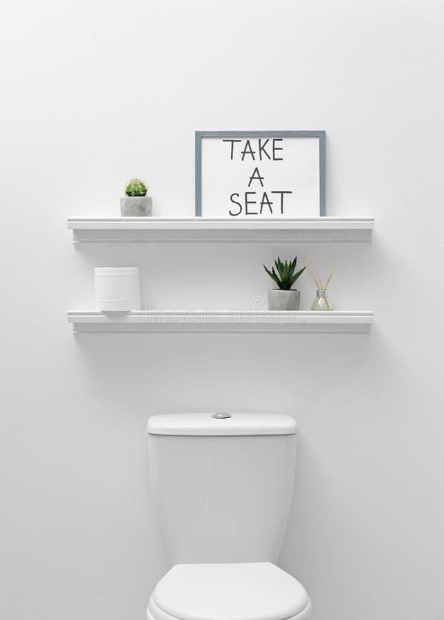 马桶、装饰元素和滑稽的标志在墙壁附近 卫生间内部 免版税库存照片