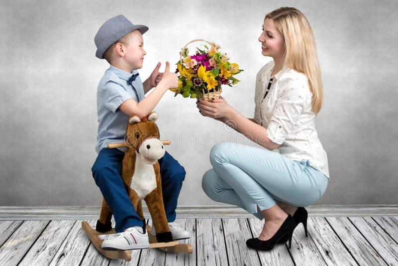 马的儿子,给花心爱的母亲篮子  在马背上小王子 春天,妇女的天,母亲节 图库摄影