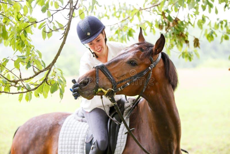 马的年轻微笑的车手妇女感人的嘴唇 免版税图库摄影