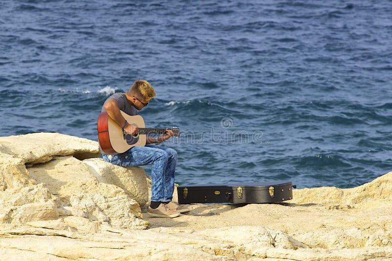 马耳他海岸的吉他演奏员 图库摄影