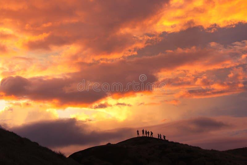 马萨亚火山火山的外缘的现出轮廓的登山人在日落的 库存图片