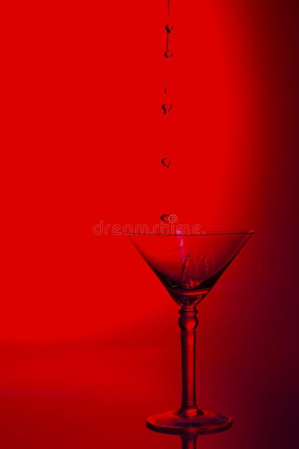 马蒂尼鸡尾酒玻璃高关键照片在演播室用红色色彩和水p 库存照片