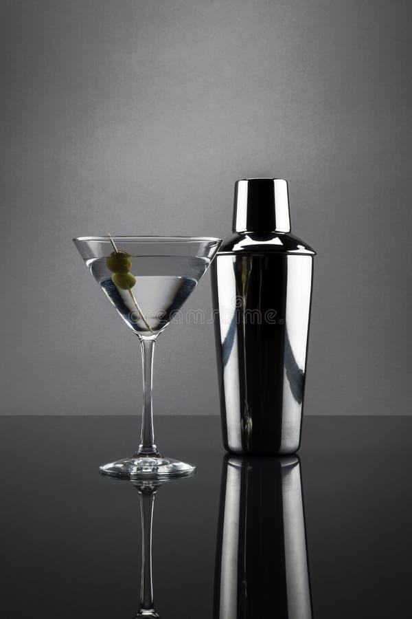 马蒂尼鸡尾酒玻璃和振动器在灰色背景 免版税图库摄影
