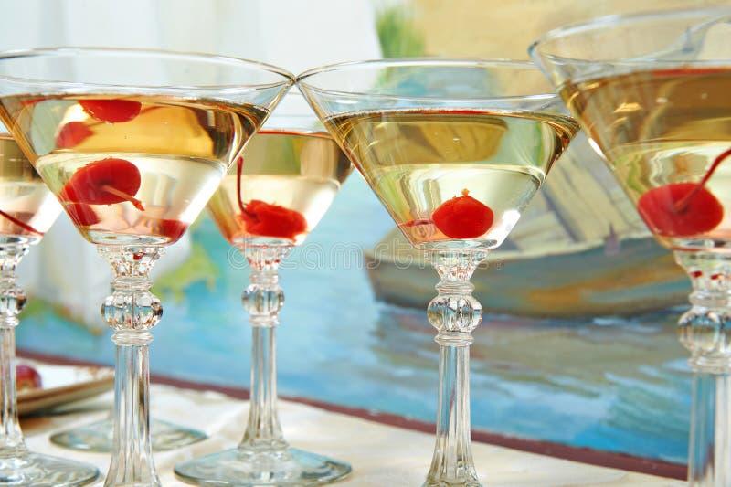 马蒂尼鸡尾酒玻璃和樱桃在节日晚会 免版税图库摄影