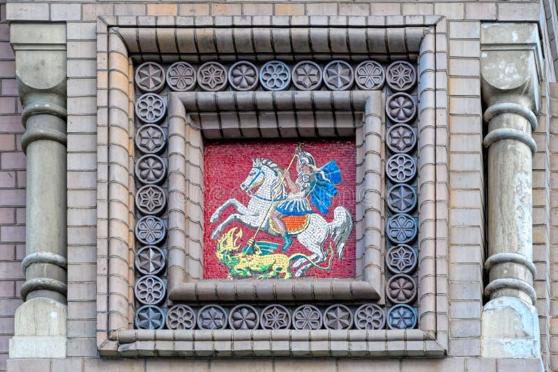 马赛克徽章在砖墙上的 库存图片
