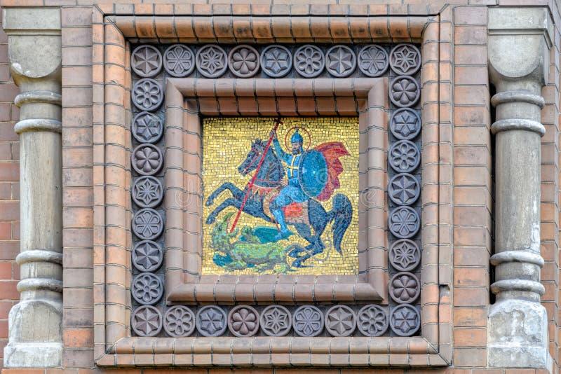 马赛克徽章在砖墙上的 图库摄影