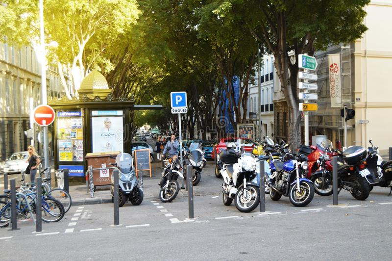 马赛,法国,2018年10月12日 众多的摩托车和滑行车在边路,秋天都市风景旁边停放 免版税库存图片