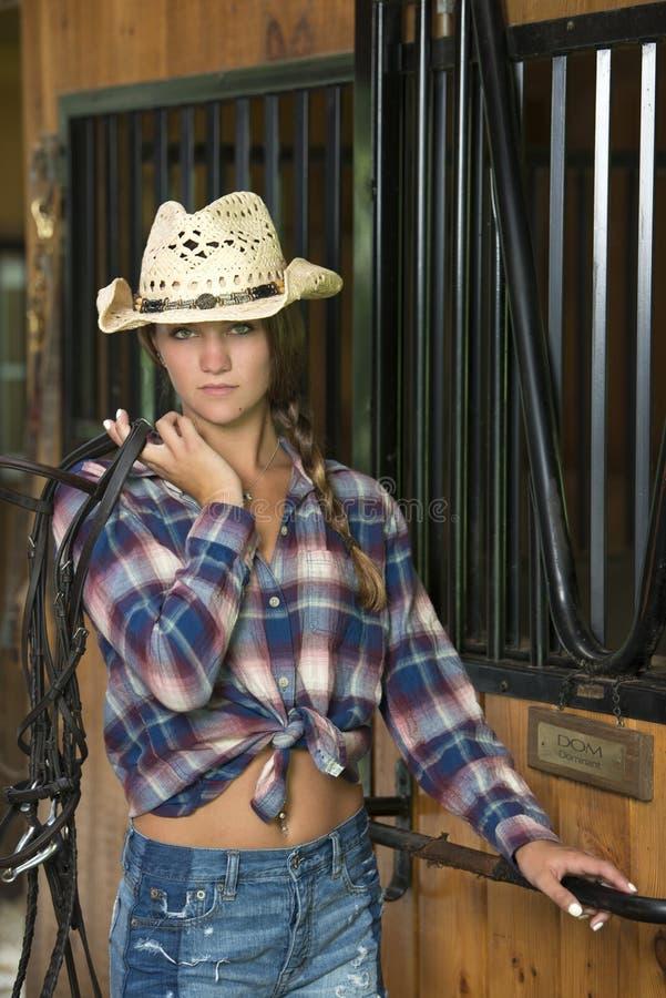 马骑术服装的逗人喜爱的青少年的女孩在谷仓摆在 库存图片