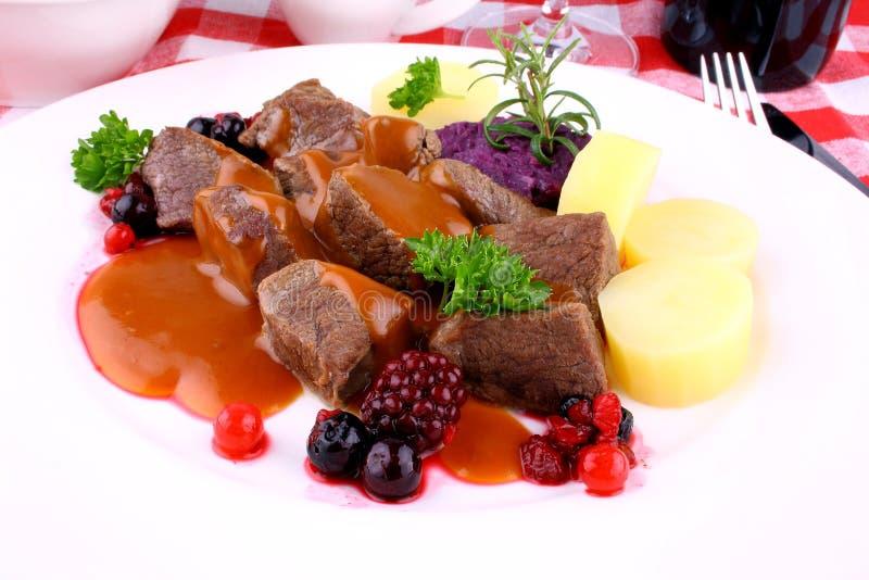 马鹿墩牛肉用土豆、伯根地调味汁和野生莓果 免版税库存照片