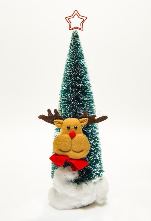 驯鹿和圣诞老人在木圣诞树附近面对 免版税库存照片