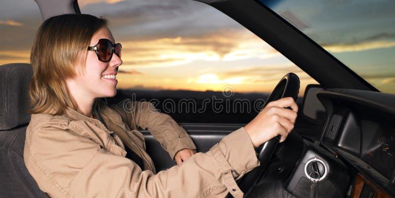 驱动佩带妇女年轻人的微笑的太阳镜 库存图片