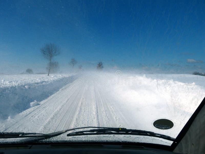 驾车在有肮脏的挡风玻璃的雪道 免版税库存照片