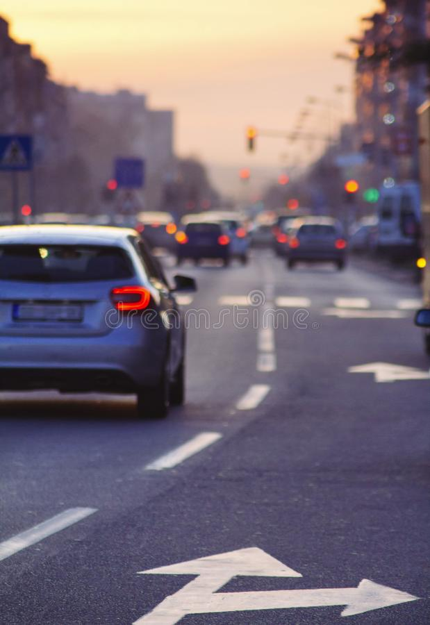 驾车在繁忙的城市道路在黄昏 免版税库存图片