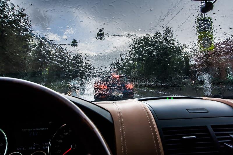 驾车在雨中 从里面的看法 在挡风玻璃的雨珠 恶劣的可见性和危险驾驶 免版税图库摄影
