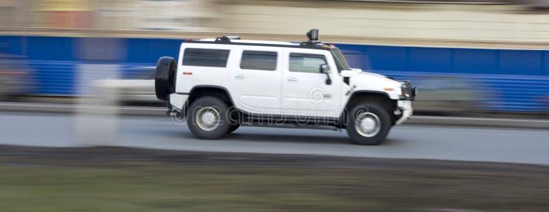 驾车快速运送巨大的发嗡嗡声的东西冲的suv白色 免版税库存图片