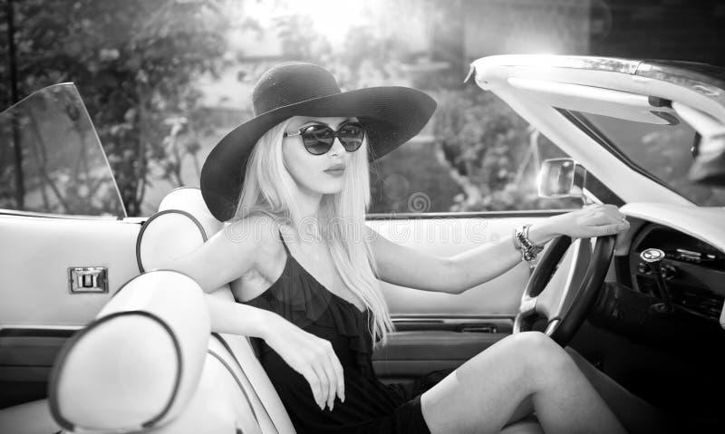 驾驶一辆敞篷车减速火箭的汽车的时髦的白肤金发的葡萄酒妇女室外夏天画象  图库摄影