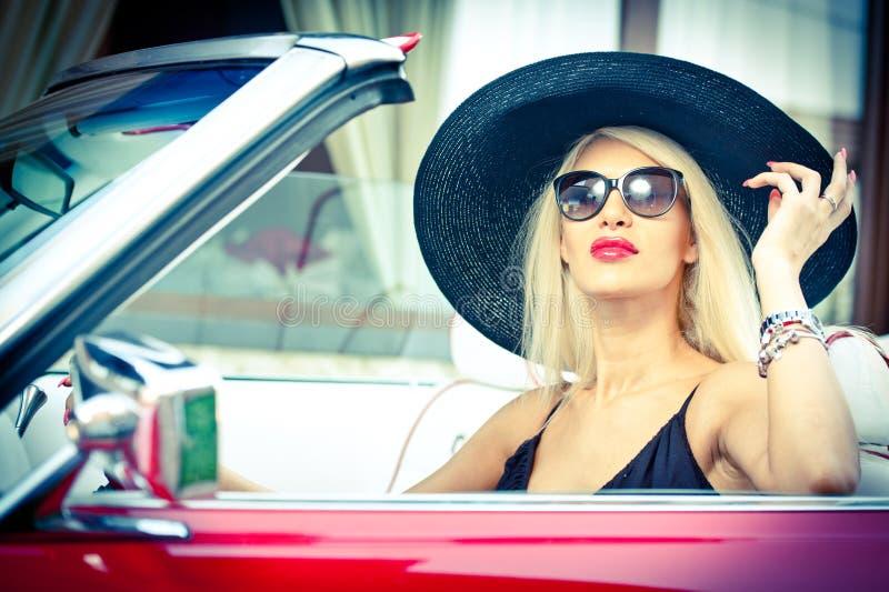 驾驶一辆敞篷车红色减速火箭的汽车的时髦的白肤金发的葡萄酒妇女室外夏天画象  时兴的可爱的公平的头发女孩 库存图片