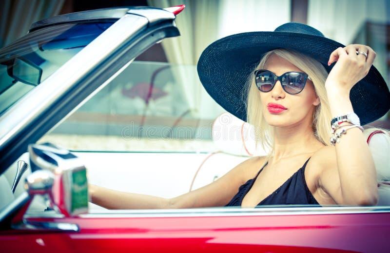驾驶一辆敞篷车红色减速火箭的汽车的时髦的白肤金发的葡萄酒妇女室外夏天画象  时兴的可爱的公平的头发女孩 免版税库存图片