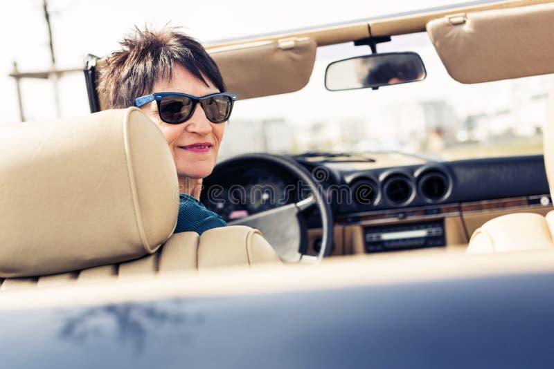 驾驶一辆敞篷车经典汽车的资深妇女 免版税库存图片