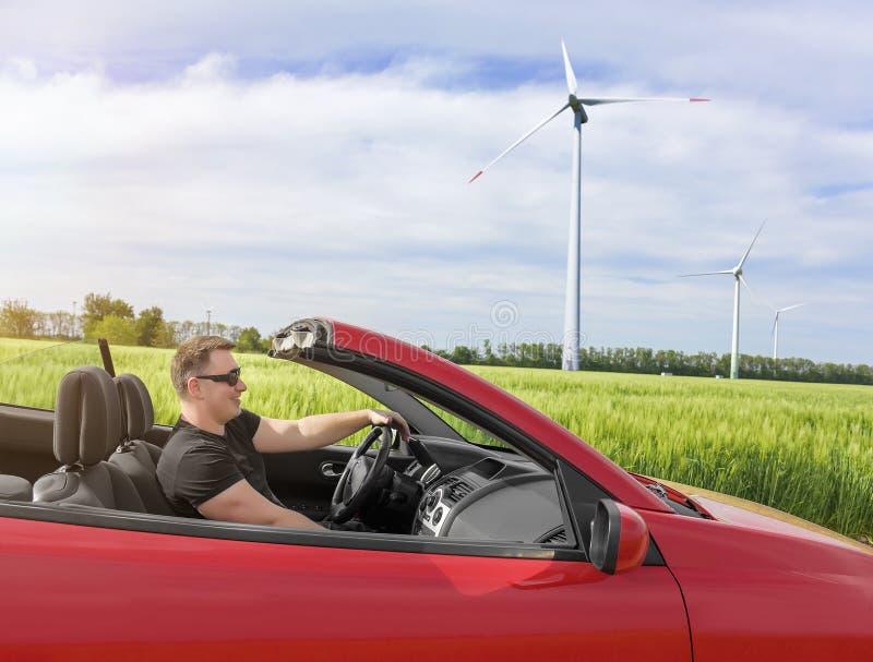驾驶一辆新的汽车的愉快的年轻微笑的人 免版税库存图片