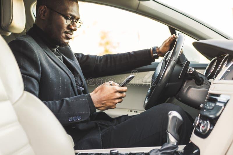驾驶一辆昂贵的汽车的商人在他的手上拿着一个手机 仓促生活 库存照片