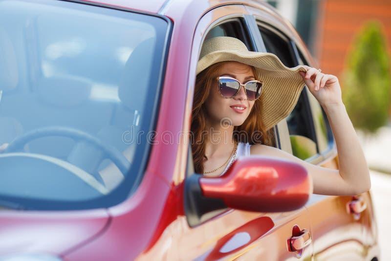驾驶一辆红色小型客车的愉快的妇女 图库摄影