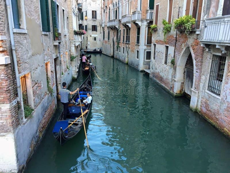 驾驶他们的在一条狭窄的安静的运河下的两名平底船的船夫长平底船在威尼斯,意大利通过老威尼斯式家 免版税库存图片