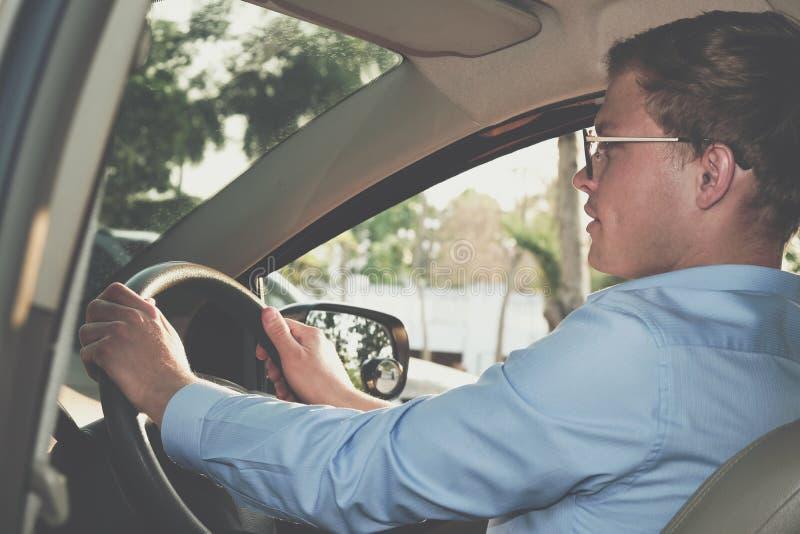驾驶他的汽车的商人 拿着方向盘的公司机 免版税库存照片