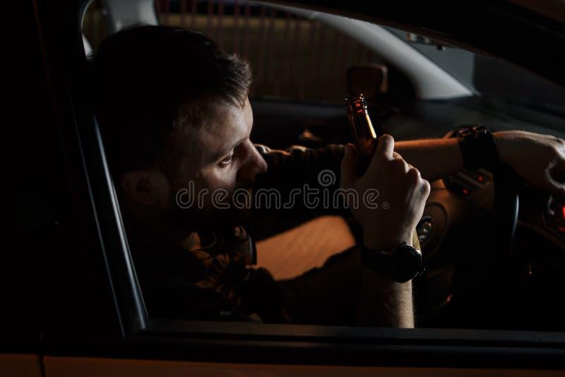 驾驶他的汽车的疲乏的年轻人 睡觉在他的汽车里面,被用尽 免版税库存照片