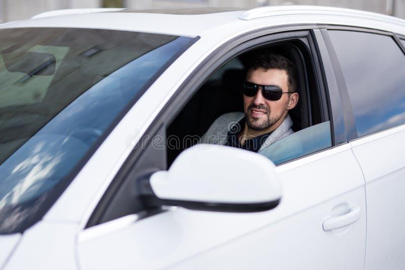 驾驶他的汽车的英俊的商人画象  免版税库存图片
