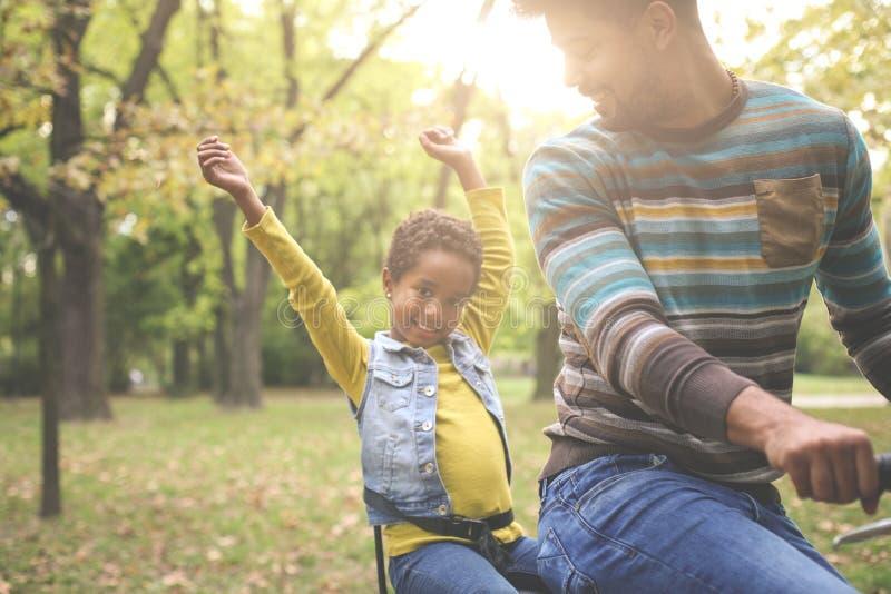 驾驶他的自行车的t的微笑非裔美国人的父亲小女孩 库存照片