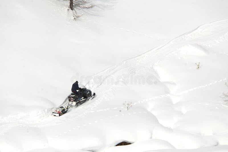 驾驶体育的人在一个晴天乘雪上电车 库存照片