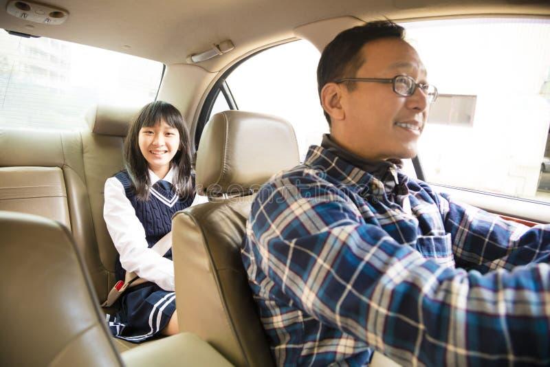 驾驶到有青少年的女儿的学校的父亲 免版税库存图片