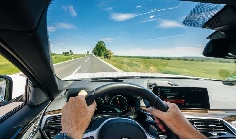 驾驶员在方向盘、行驶、公路上驾驶的手 免版税图库摄影