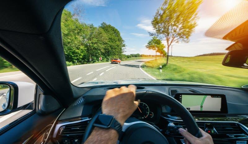 驾驶员在方向盘、行驶、公路上驾驶的手 免版税库存图片