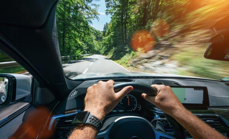 驾驶员在方向盘、行驶、公路上驾驶的手 库存照片