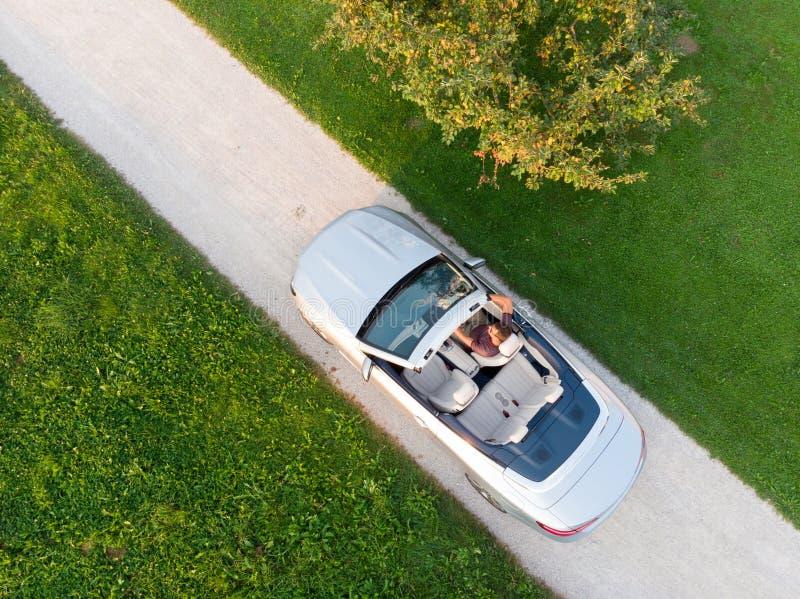 驾驶和享用他的在空旷地区边的成功的人鸟瞰图银色敞篷车豪华跑车 免版税库存照片