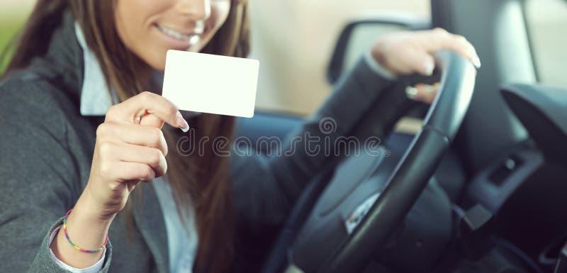 驾驶和拿着名片的少妇 免版税库存图片