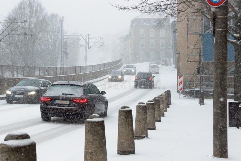 驾驶在一条积雪的街道上的汽车在降雪在德国 免版税库存照片
