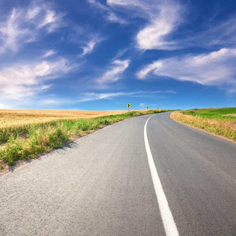 驾驶在一条空的柏油路晴天 免版税库存照片