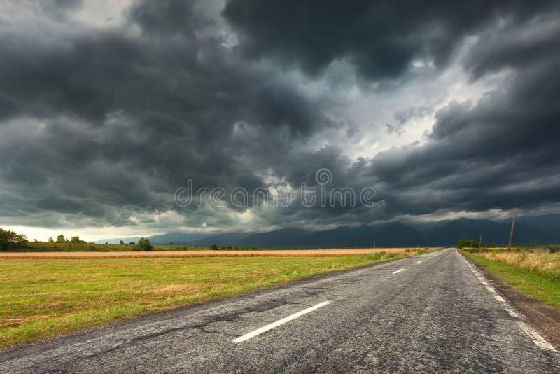 驾驶在一条空的老路在多暴风雨的天气 免版税图库摄影
