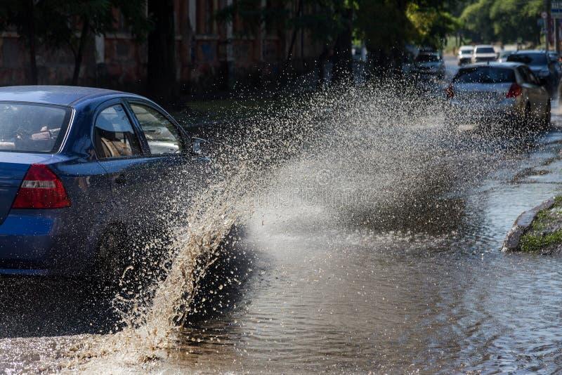 驾驶在一条被充斥的路的汽车在雨造成的洪水期间猛冲 在水的汽车浮游物,充斥街道 在机器的飞溅 免版税图库摄影