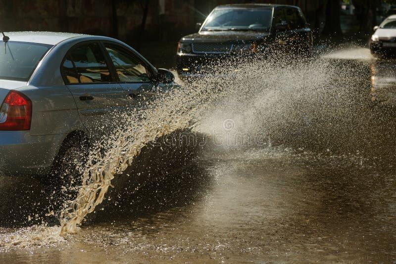 驾驶在一条被充斥的路的汽车在雨造成的洪水期间猛冲 在水的汽车浮游物,充斥街道 在机器的飞溅 免版税库存图片