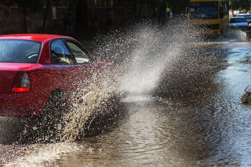 驾驶在一条被充斥的路的汽车在雨造成的洪水期间猛冲 在水的汽车浮游物,充斥街道 在机器的飞溅 免版税库存照片