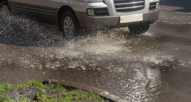 驾驶在一条被充斥的路的汽车在雨造成的洪水期间猛冲 在水的汽车浮游物,充斥街道 在机器的飞溅 库存图片