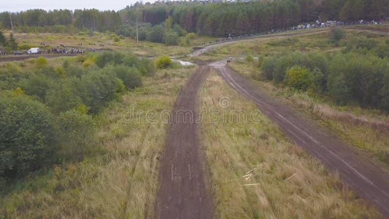 驾驶在乡下公路的SUVs顶视图 夹子 越野赛跑在泥路在农村森林区域 库存图片