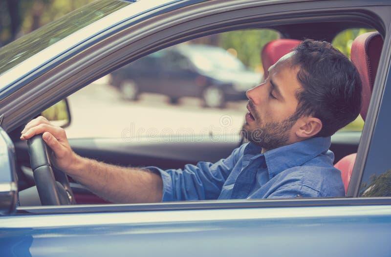 驾驶在交通的困疲乏的被疲劳的被用尽的人汽车在长时间驱动以后 免版税库存照片