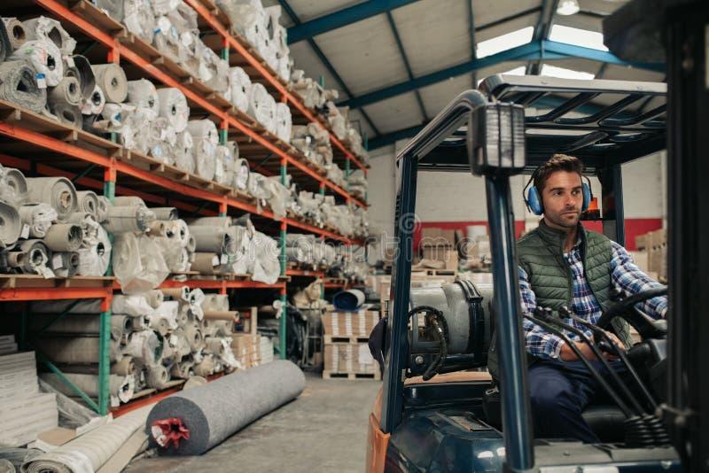 驾驶在仓库地板上的工作者一辆铲车 库存照片