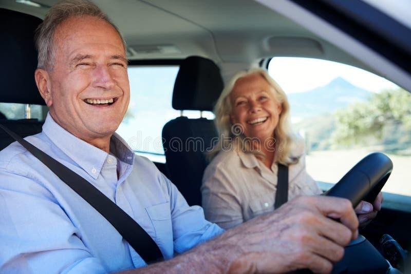 驾驶在他们的汽车的愉快的资深白色夫妇,微笑到照相机,侧视图,关闭  免版税图库摄影