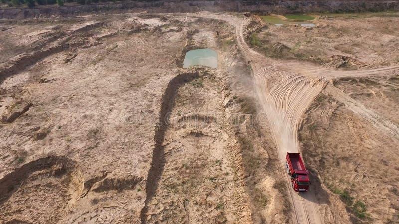 驾驶在农村路的卡车顶视图 ?? 在干燥黄色猎物路的翻斗车乘驾在夏天 大量手段 免版税库存图片